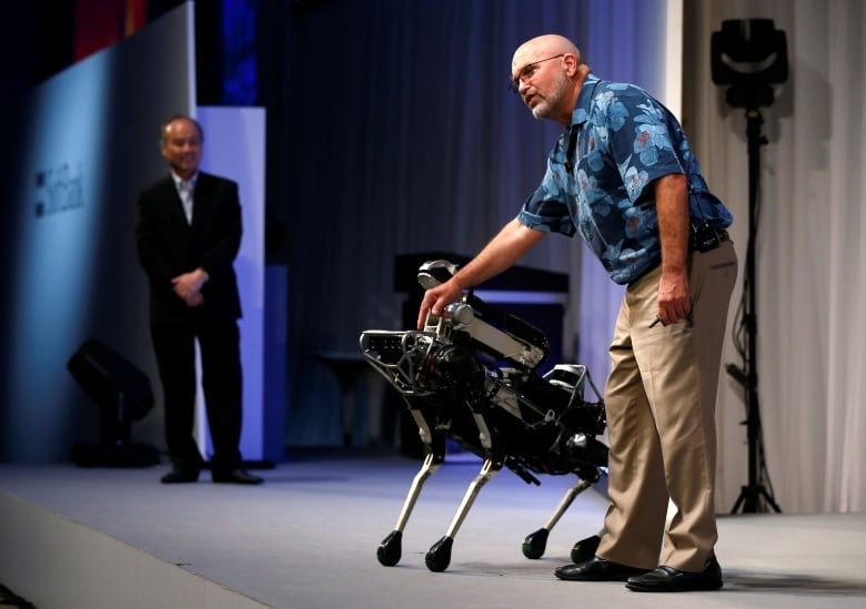 Boston Dynamics CEO and founder Marc Raibert, seen with the SpotMini robot, says he doesn